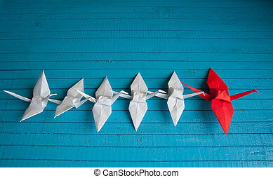 lot of white cranes and 1 red on the board
