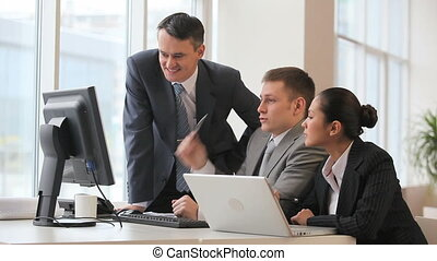 Boss checks the work of colleagues