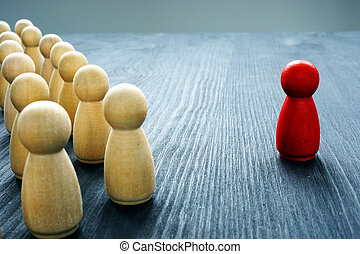 Leadership concept. Crowd of wooden figures and red one.