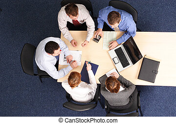 Businesspeople gathered around a table for a meeting, brainstorming. Aerial shot taken from directly above the table.