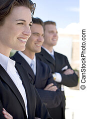 Leadership - one female two males wearing dark business...