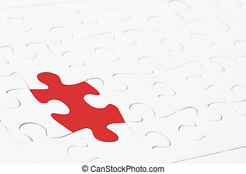 Leadership or thinking different concept. Close up red jigsaw puzzle in the midst of white.