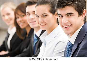 Leadership - Smiling businessman looking at camera with...