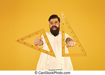 Leading engineer of the project. Smart engineer holding triangles on yellow background. Teaching engineer smiling with drawing instruments ready for working. Happy engineer or designer