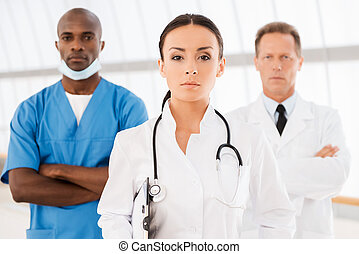 Leading her team. Beautiful female doctor holding clipboard...
