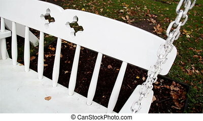 Leaf on top of the white bench swing