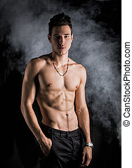 Lean athletic shirtless young man standing on dark ...