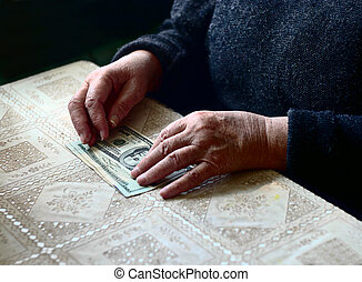 Lean purse. Old woman's hands and dollar bills on table, contrast shot, selective focus, very shallow DOF