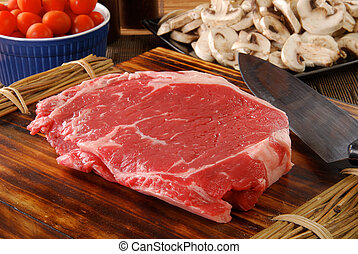 Lean raw rib steak - a lean uncooked rib steak on a cutting ...