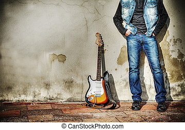 leaning on the wall with an electric guitar