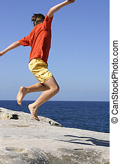 Leap for Joy - Boy leaps into the air with outstretched arms