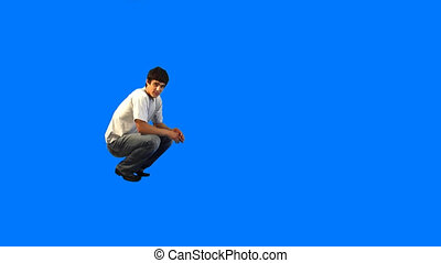 Leap - Handsome guy jumping on blue background in studio