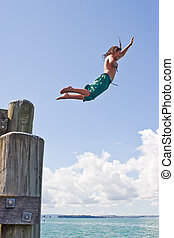 A teenage boy leaps off the wharf at Rangitoto Island in the Hauraki Gulf of New Zealand