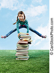 Leaping through stack - Image of happy girl jumping on the...