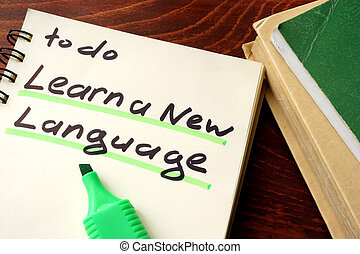 Learn a new language written on a notepad. Education...
