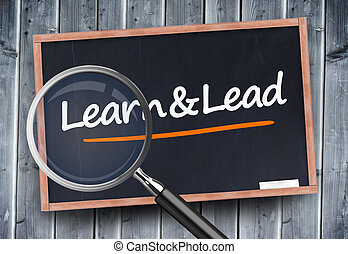 Learn and lead written on a blackboard with magnifying glass...