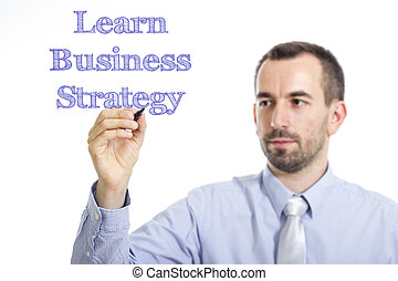 Learn Business Strategy - Young businessman writing blue text on transparent surface