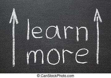 learn more phrase handwritten on school blackboard