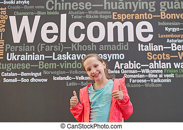 Smiling little girl in front of welcome board gesturing thumbs up, with a word Welcome in different languages