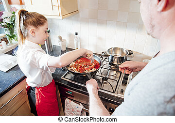 Little girl is learning how to cook with her father at home. They are making a spagetti bolognese together.