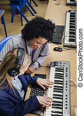 Learning Keyboard In Music Lesson - Female teacher is...