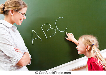 Learning letters - Image of smart girl pointing at letter on...