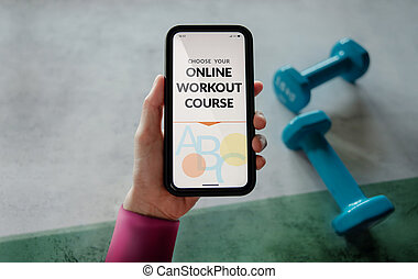 Learning Online Workout Concept. Young Woman using Mobile phone to choosing an Exercising Course. Dumbbell on the floor as background