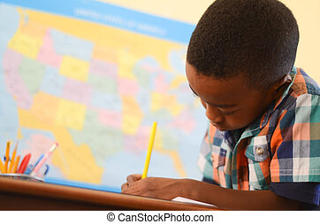 Learning - An African American young boy doing work in...