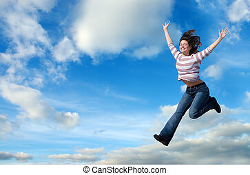 Learning to fly - Beautiful woman jumping against blue sky
