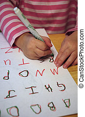 Learning to Write - Little child writing on paper practicing...