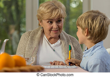 Learning with granny - Happy little boy learning at home...