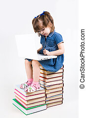 Learning with laptop - Photo of schoolgirl sitting on books...