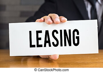Leasing, message on white card and hold by businessman