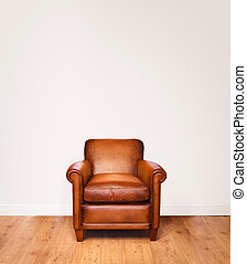 Leather armchair on a wooden floor against a white...