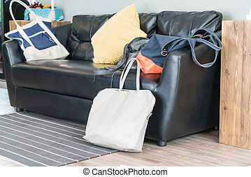 bag on black leather sofa