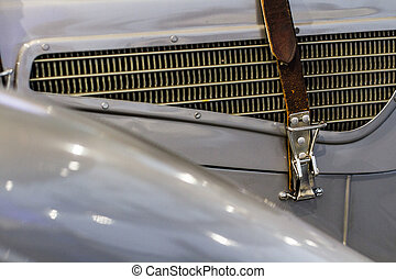 Leather belt on vintage oldtimer gray car on radiator grill and polished furniture