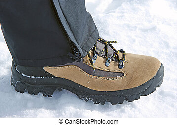 Leather boot with black laces on snow.