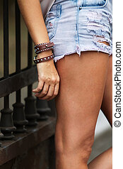 Leather bracelet with spikes and torn jeans - Fashionable...