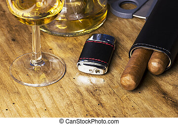 Leather case with cigars, bottle and glass of whiskey, lighter and cigar cutter on an wooden board