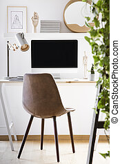 Leather chair standing by wooden desk with mockup monitor, metal lamp and decor in real photo of home office corner in white room interior