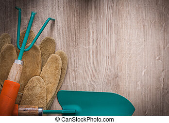 Leather gardening gloves metal hand spade and rake on wood board