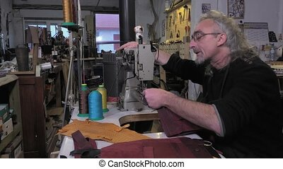 leather goods craftsman at work - assembled with a triple...