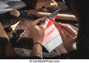 Leather handbag craftsman at work in a workshop