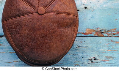 leather headgear - hat hanging on a wooden wall.