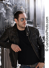 Sexy guy with attitude wearing leather jacket and sunglasses outdoors