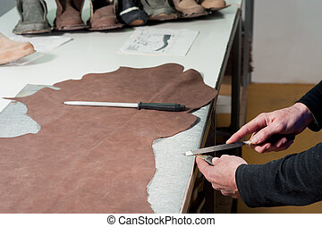 Leather manufacture worker sharpening his traditional...