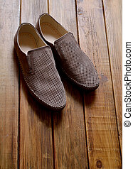 Leather men's shoes with perforation on the wooden background.