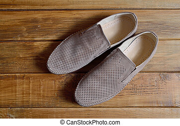 Leather men's shoes with perforation on the wooden background