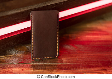 Leather phone case on a wooden background in neon light