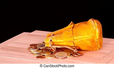 Leather pouch and euro coins are rotated on the table.